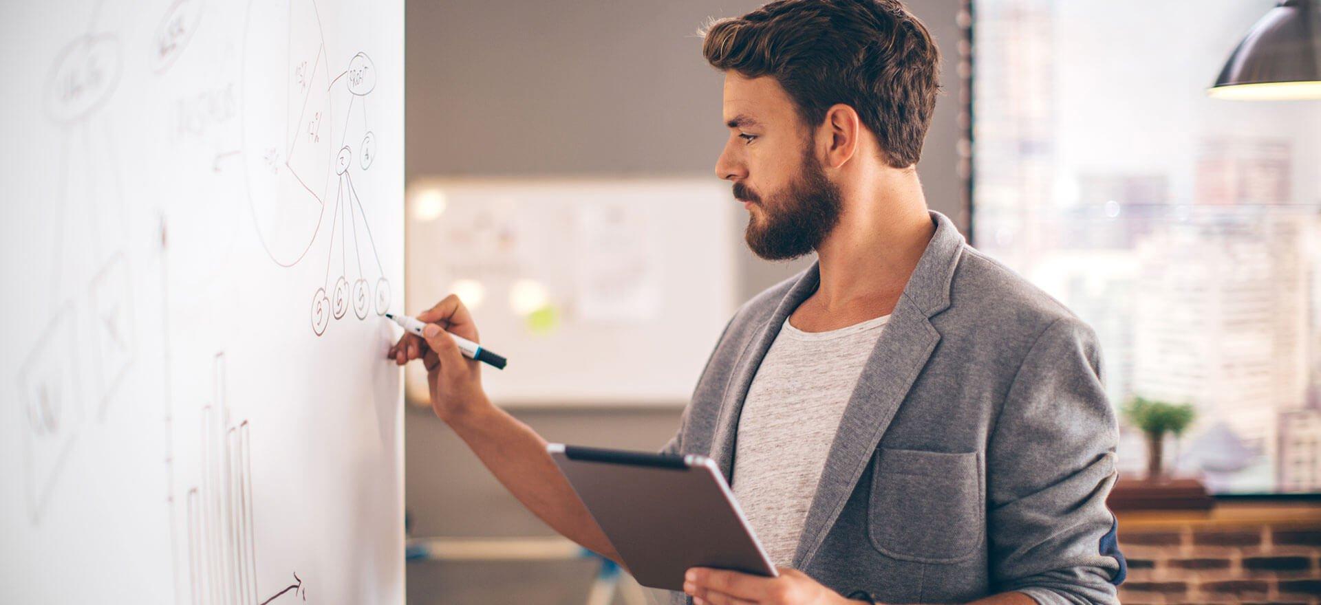 Man calculating financial ratios on whiteboard