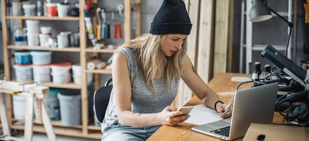 woman sitting at a desk and considering emergency business finance options