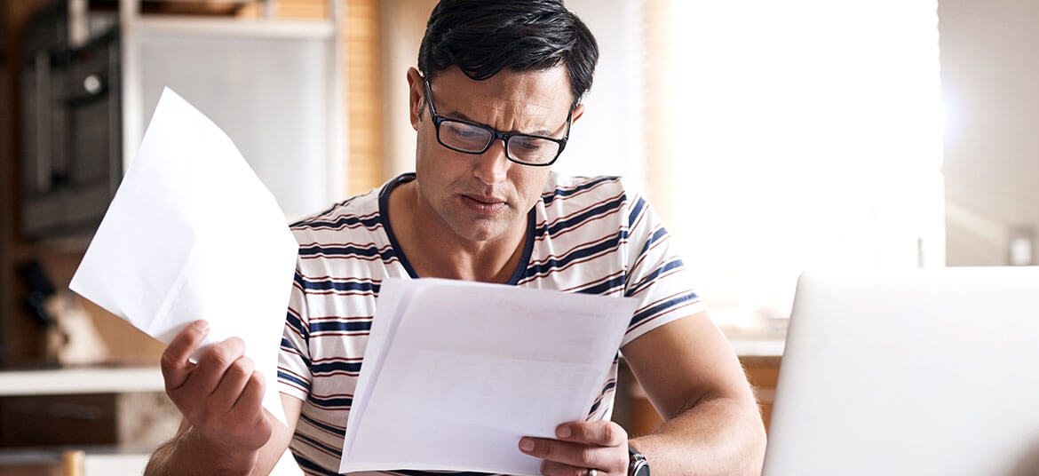 Picture of man examining papers with current liabilities