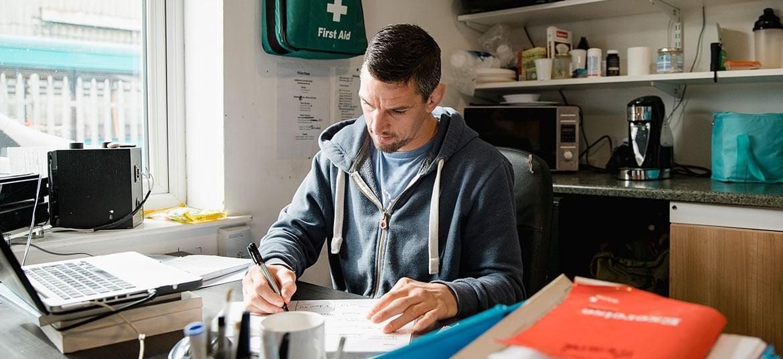 Man sitting at desk writing a business plan