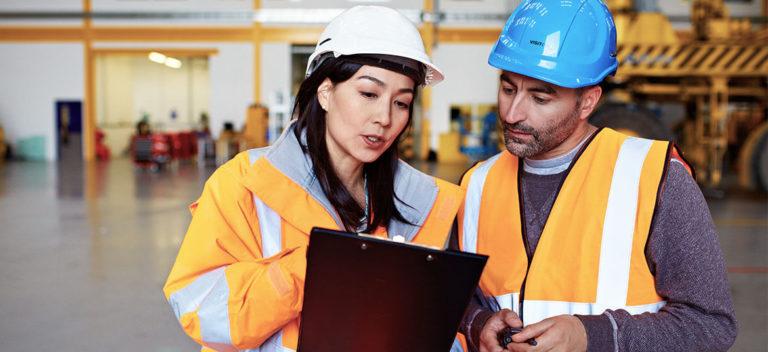 Staff In Warehouse Discussing Debtor Finance