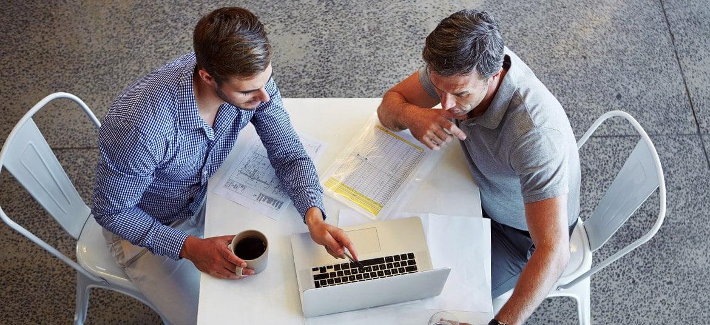 Businessmen at a computer calculating APR vs Simple Interest Rate using the simple interest rate formula